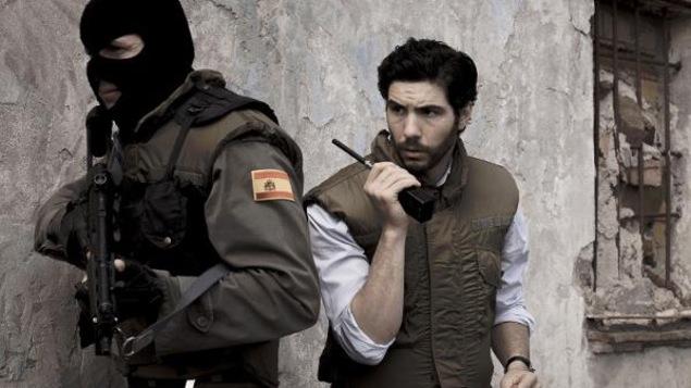 Un homme avec un talkie-walkie derrière un soldat armé et cagoulé.