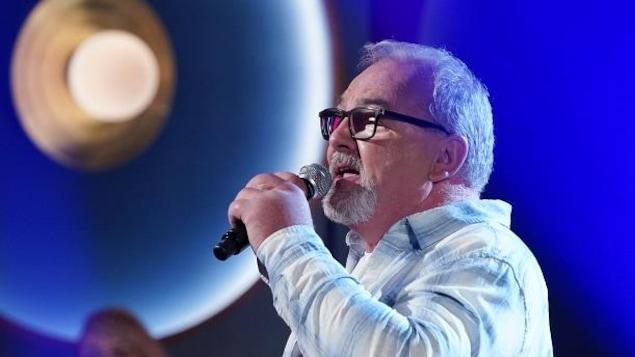 Un homme qui chante, micro à la main.