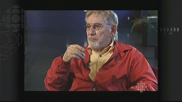 Un homme portant un blouson rouge, assis.