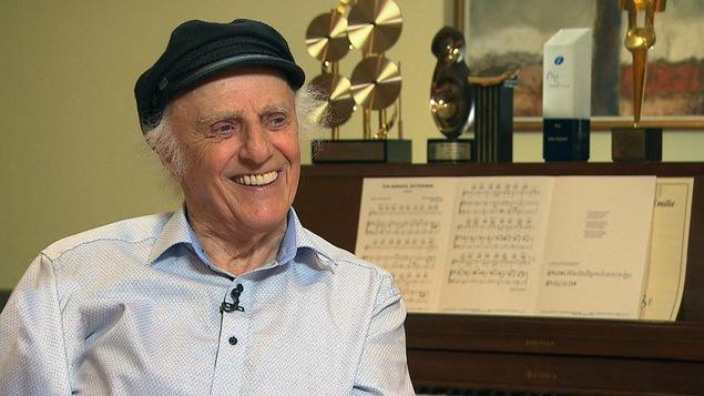 Gilles Vigneault en entrevue chez lui, en novembre 2017, à 89 ans. Il porte une casquette et est assis au piano.