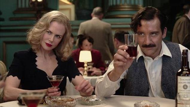 Un couple, à table, avec des verres de vin.