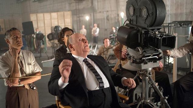 Un réalisateur assis sur sa chaise derrière sa caméra.