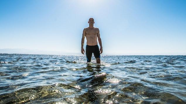 Un homme torse nu marche dans la mer.