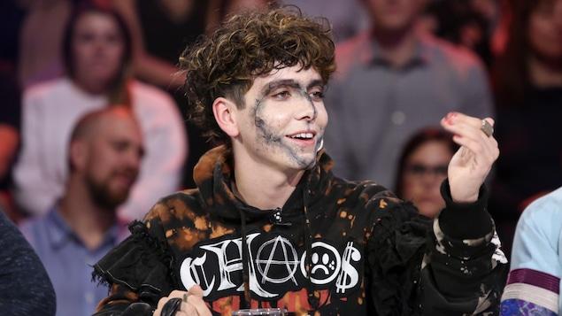 Hubert affiche un maquillage en forme de coeur, qui encadre son visage. Il porte un costume flamboyant.