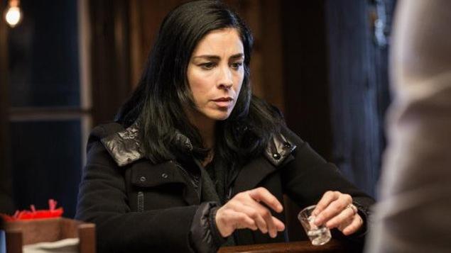 Une femme en manteau, derrière un bar, un verre à la main.
