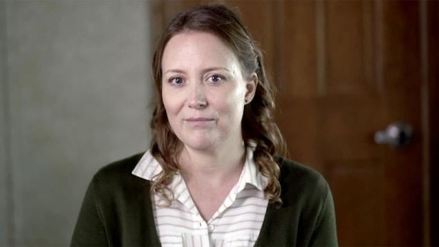 Isabelle Blais porte une chemise à rayures et un chandail vert.