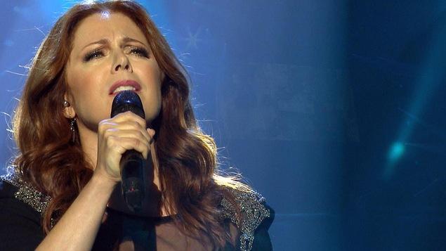 La chanteuse tient un micro dans les mains sur une scène.