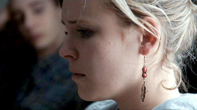 Une jeune femme avec une boucle d'oreille, en gros plan,de profil.