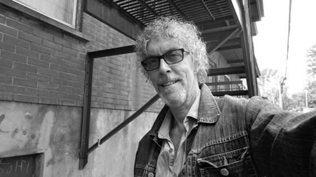 Un homme frisé avec des lunettes et une veste en jeans fait un égoportrait.