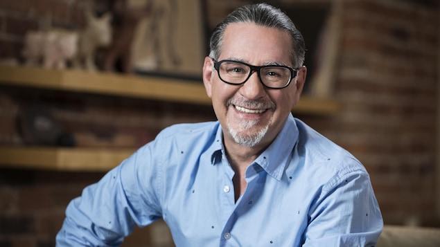 Un homme dans une pièce avec un mur de brique, il est souriant et porte des lunettes et les cheveux tirés vers l'arrière.
