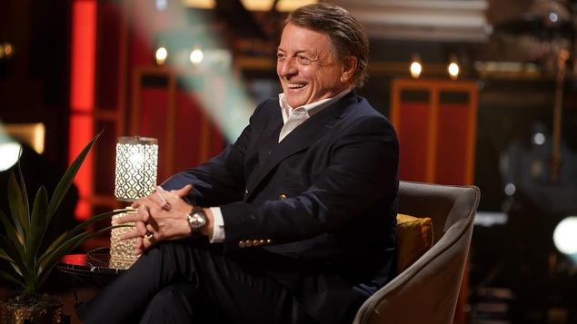Un homme qui porte une chemise blanche et un veston bleu marine. Il sourit.