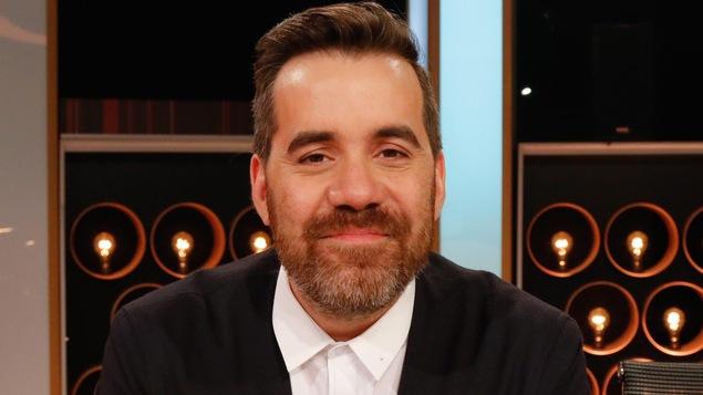 Portrait d'un des échangistes sur le plateau de l'émission. Il porte un joli veston et une chemise blanche.