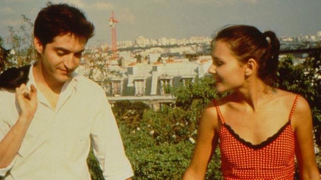 Un jeune couple se tient la main, en surplomb de toits