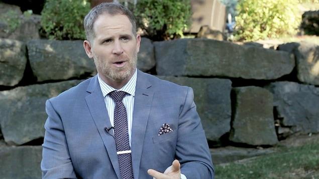 Il porte une chemise blanche à fines rayures bleues, une cravate et un veston bleu.