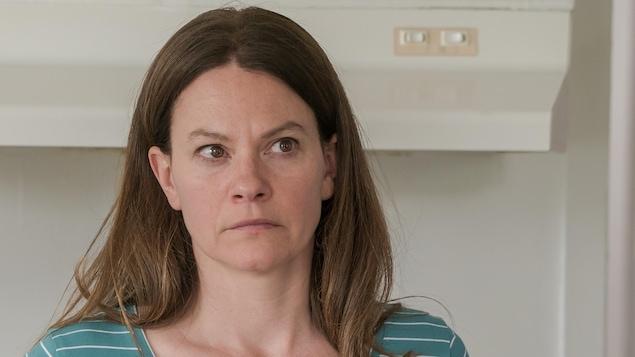 La femme est sérieuse. Elle a les cheveux châtains foncés et les yeux bruns. Elle porte un chandail vert à fines lignes blanches.
