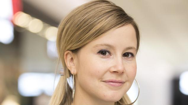 Une jeune femme qui sourit. Ses cheveux sont blonds et attachés en deux couettes. Elle porte de grands anneaux.