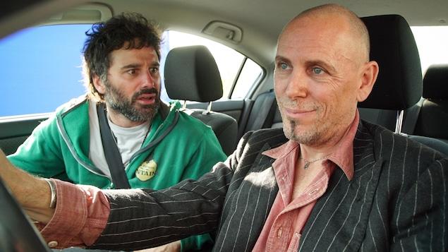Kevin et Marc sont dans une voiture. Kevin a l'air apeuré et Marc à sourire narquois.