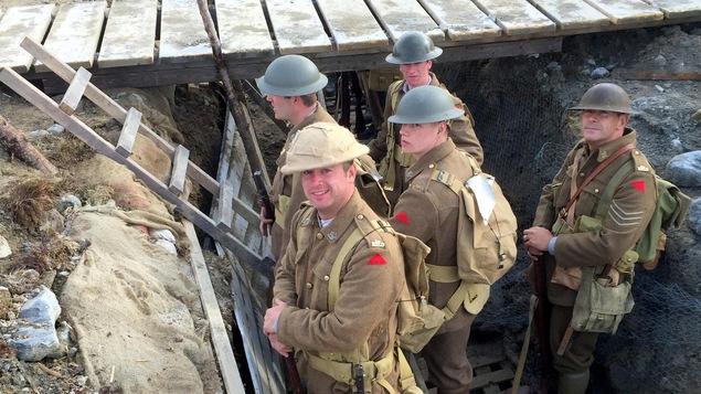 Des soldats dans les tranchées humides regardent la caméra.