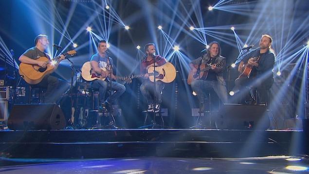 Stéphane Yelle, Jonathan Painchaud, Steeve Vielleux, Jean-François Dubé et Boom Desjardins sont en prestation avec leur guitare sur le plateau de La fureur.