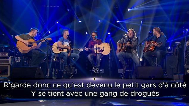 Jean-François Dubé, Jonathan Painchaud, Stéphane Yelle, Steeve Vielleux et Boom Desjardins sont assis sur des tabourets avec leur guitare sur le plateau de La fureur.