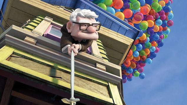 Un vieil homme penché par la fenêtre d'une maison que tirent des ballons multicolores.