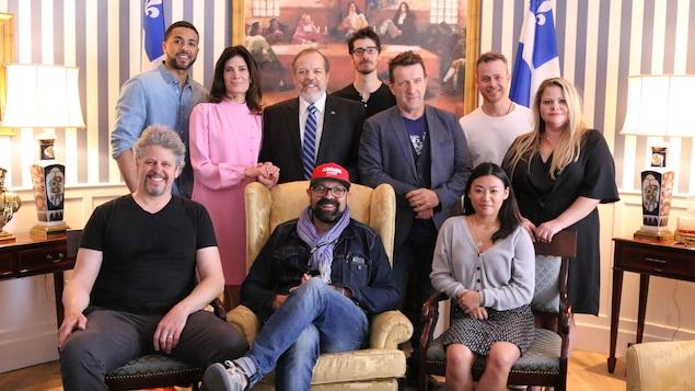 Une dizaine de personnes de la distribution, incluant le producteur et le réalisateur prennent la pose dans le salon oval ede la Maison Bleue.