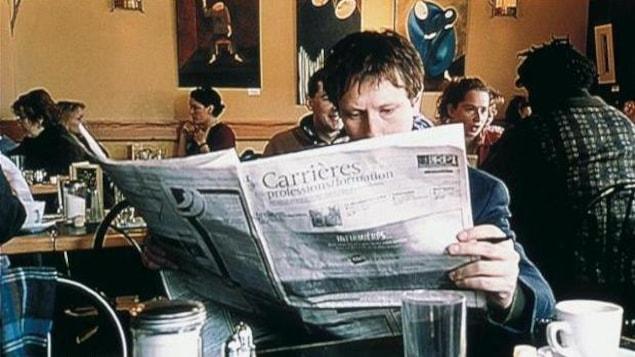 Un homme, dans un café, lit son journal.