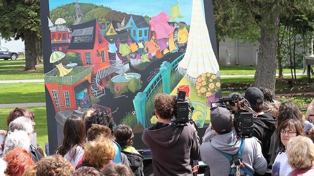 Des caméra filment un grand tableau dans un parc.