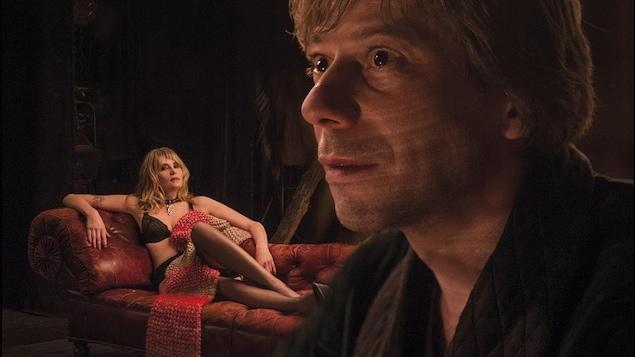 Une femme en sous-vêtements allongée sur un canapé, un homme regardant au loin au premier plan.