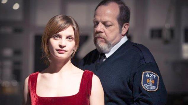 Un homme en tenue de gardien de sécurité derrière une jeune femme en robe rouge.