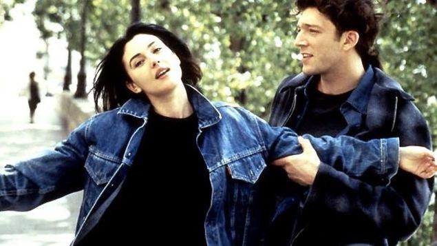 Une jeune femme les bras ouverts retenue par un jeune homme, à l'extérieur.