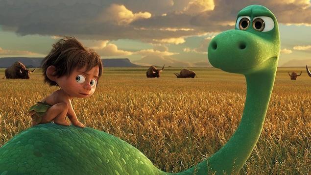 Un petit garçon sur le dos d'un dinosaure, tous deux face à des buffles.