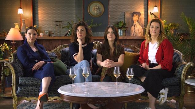 Quatre femmes assises dans un canapé antique, devant elles, une table contient quatre verres de vin blanc.