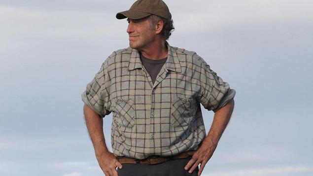 Un homme en chemise, les mains sur les hanches, une casquette sur la tête.