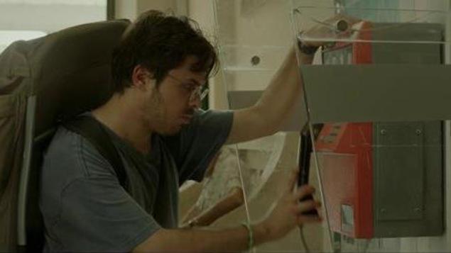 Le personnage de Ricardo Trogi, sac au dos, raccroche le combiné dans une cabine téléphonique.