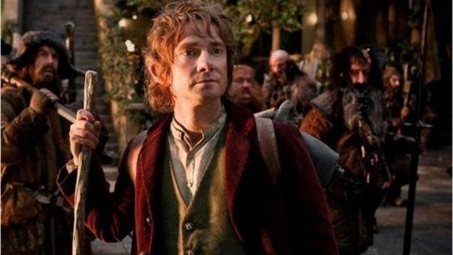 Un hobbit tenant un bâton de marche, devant d'autres créatures prêtes à aller marcher.