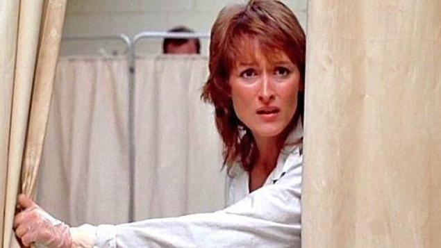 Une femme (Meryl Streep) derrière un rideau blanc qu'elle ouvre d'une main portant un gant de plastique.