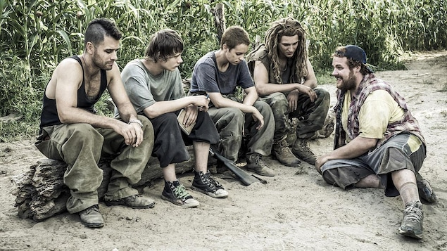 5 jeunes assis dans le sable ou sur un tronc, devant un champ de maïs.