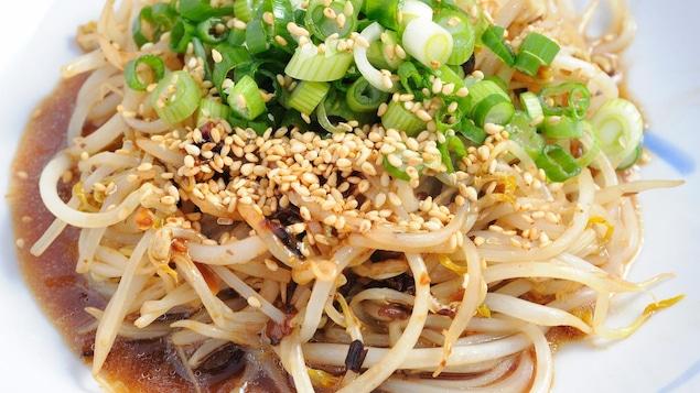 Un plat de fèves germées garni de graines de sésames et échalottes.