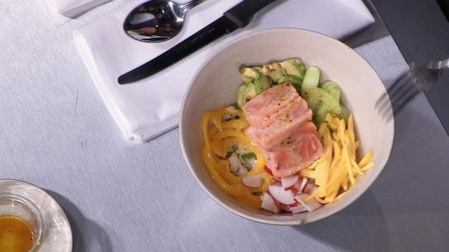 Bol de poke au saumon avec légumes et vinaigrette d'accompagnement.