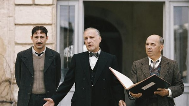 Trois hommes (Kad Merad, François Berléand et Gérard Jugnot) en tenues strictes, sur le parvis d'une école.