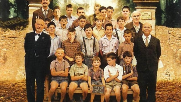 Deux hommes (Gérard Jugnot et François Berléand) encadrent des enfants pour une photo de classe.