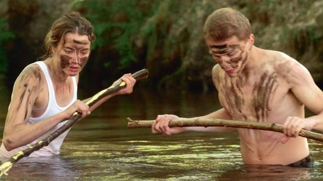 Une jeune femme et un jeune homme maculés de boue, avec des batons, dans l'eau jusqu'à la taille.