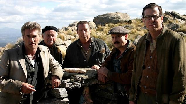Cinq hommes (dont Roy Dupuis, Claude Legault et Patrice Robitaille) en extérieur.