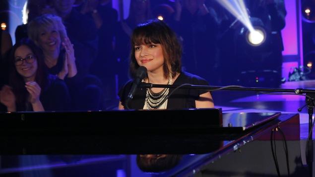 La chanteuse et musicienne est assise au piano et sourit.