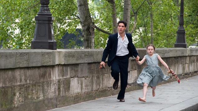 Sur un pont, un homme (Tahar Rahim) court en tenant une petite fille par la main.