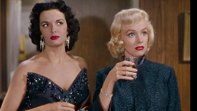 Une femme brune et une femme blonde regardent devant elles, interloquées.