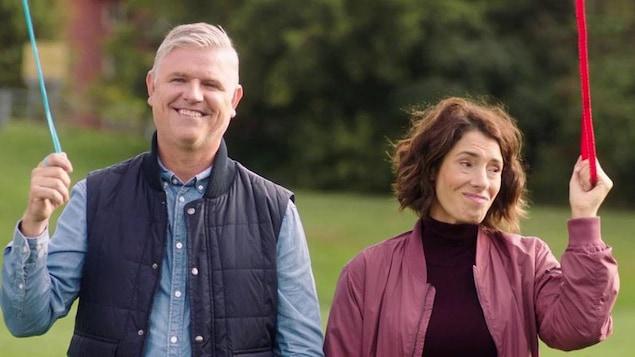 Un homme et une femmes sont dans un parc et tiennent une laisse à perruches.