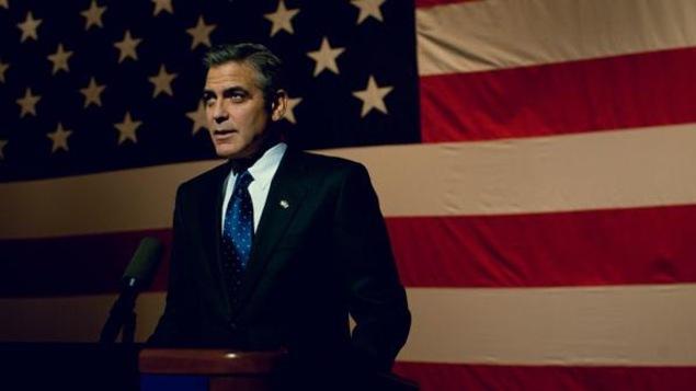 Un homme devant un pupitre, un immense drapeau américain derrière lui