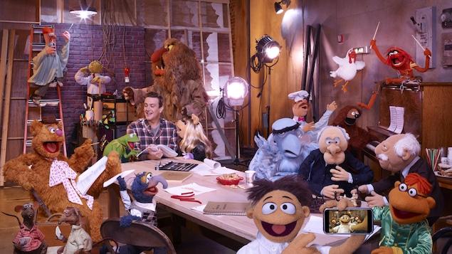 Les marionnettes des Muppets entourent Jason Segel sur un plateau de tournage encombré